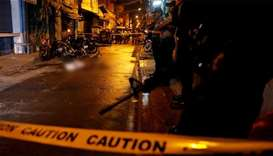 Policemen stand guard near the body of a man killed during a drug related killing in Pasig