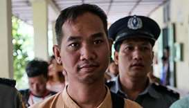 Swe Win (C), the editor of Myanmar Now, is escorted to a court by police