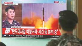 A South Korean soldier watches a news programme showing file footage of a North Korean missile launc