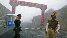 Chinese soldier (L) next to an Indian soldier at the Nathu La border crossing between India and Chin