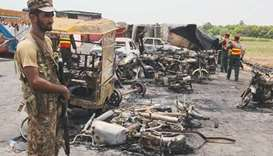 Pakistani soldiers stand guard beside burnt out vehicles at the scene where an oil tanker caught fir
