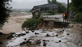 Rescue workers walk at an area hit by heavy rain at Haki district in Asakura, Fukuoka Prefecture, Ja