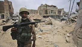 An Iraqi Counter-Terrorism Service (CTS) member stands guard in the old city of Mosul on July 7, 201