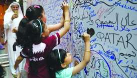 Children writing their messages on a billboard near the Mamoura Complex in Doha.