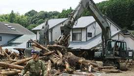 Defence forces soldiers remove debris in a flooded area in Asakura, Fukuoka prefecture.