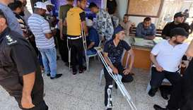Hamas officials register the passport details of injured Palestinians preparing to board a blockade-