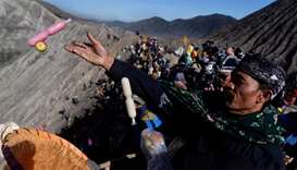 Worshippers throw offerings into the volcanic crater of Mount Bromo