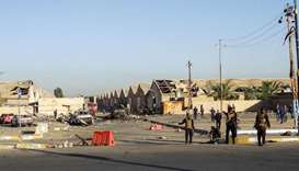 Members of the Iraqi Counter-Terrorism Service (CTS) stand at the scene of an attack outside warehou