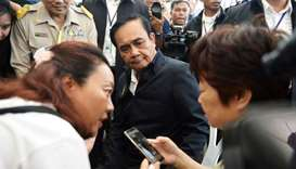 Thailand's Prime Minister Prayuth Chan-ocha sits next to a relative of Chinese tourists involved in