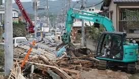 A worker removes the roof blocking a road in the flood hit area Mabicho in Kurashiki, Okayama prefec