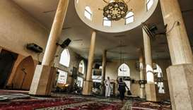 Palestinian men inspect damages to a mosque that was hit by Israeli air strikes the day before in Ga