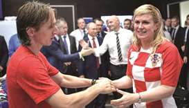 Kolinda Grabar-Kitarovic (right) greets captain Luka Modric