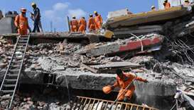Members of the National Disaster Response Force search for victims after an under construction build