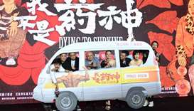 Director Wen Muye poses for a picture with cast members and crew of the movie Dying To Survive