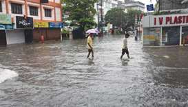 Two men make their way through a flooded street in Kochi.