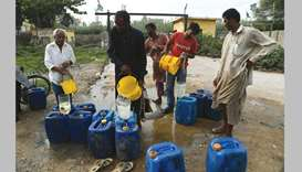 DEAR WATER: This photo taken on July 17 shows residents filling their containers with water in Karac