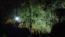 Thai soldiers stand at the mouth of Tham Luang cave, at the Khun Nam Nang Non Forest Park in Chiang