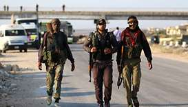 Syrian rebel fighters from the Quneitra province walk with their rifles as they wait at the Murak cr