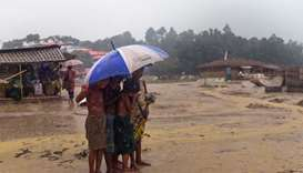 Rohingya refugee children shelter under an umbrella during a rain storm at Balukhali refugee camp in