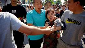 A woman is detained by security personnel outside the US embassy in Beijing