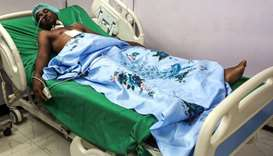 An injured Yemeni fisherman lies in a hospital bed as he receives treatment after being wounded in a
