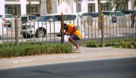 A person 'squeezing' through a gap along the median fence on Grand Hamad Street