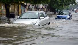 Indian commuters make their way on a flooded road following heavy rain in Mathura on Thursday in Ind