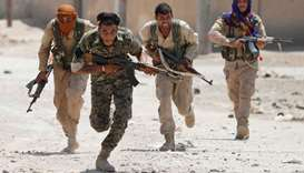 Kurdish fighters from the People's Protection Units (YPG) run across a street in Raqqa