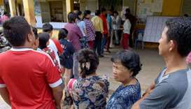 Cambodians wait in line to vote at a polling station during the country's sixth general election in