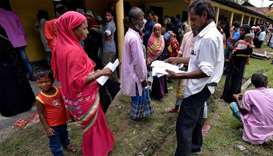 Villagers wait outside the National Register of Citizens (NRC) centre to get their documents verifie