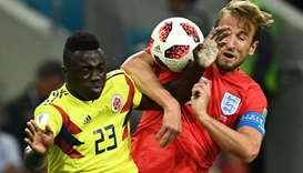 Colombia's defender Davinson Sanchez (L) heads the ball as he vies for it with England's forward Har