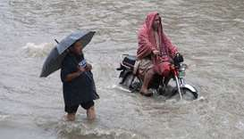 A man holds an umbrella as he walks through floodwaters during heavy rain in Lahore