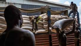 Employees at World Food Programme (WFP) warehouse, situated near Juba Airport, prepare food sacks