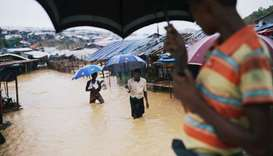 Rohingya refugees walk along the water as parts of the Kutupalong camp flooded during heavy rain in