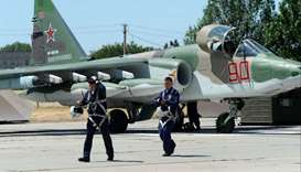 Su-25 fighter jet pilots, who took part in the Russian mission in Syria, walk on the runway after la
