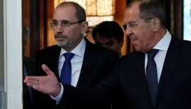 Russian Foreign Minister Sergei Lavrov and Jordanian Foreign Minister Ayman Safadi enter a hall duri