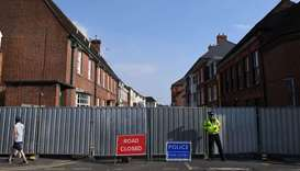 A police officer stands guard at a barrier across Rollestone Street outside the John Baker House San