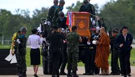 A buddhist monk leads an honour guard carrying the coffin of Samarn Poonan