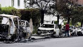 A resident looks at the wreckage of burnt-out cars in the Bellevue neighborhood in Nantes