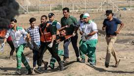 Palestinian paramedics carry a wounded person away from the scene of clashes with Israeli forces