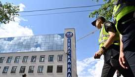 "Police officers pass by the ""112 Ukraine"" tv channel damaged facade, after the building was attacked"