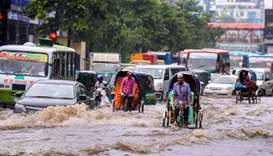 Bangladeshi rickshaw pullers make their way through heavy rainfall at a water-logged street during t
