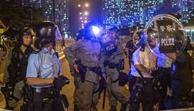 A laser beam is shown on the face of a police officer as protesters occupy the main road of the dist