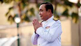 Thailand's Prime Minister Prayuth Chan-ocha greets people as he arrives for a photo session with the
