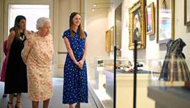 Britain's Queen Elizabeth II looks at a dress worn by Albert Edward, Prince of Wales (later King Edw