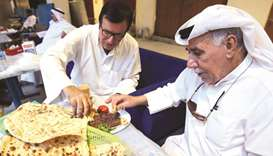 Kuwaiti Hassan Abdullah Zachriaa, owner of Al-Walimah restaurant, shares Iranian bread during a meal