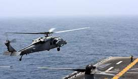 An MH-60S Sea Hawk lands on the flight deck of USS Boxer (LHD-4) in the Arabian Sea off Oman