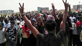 Sudanese protesters chant slogans and wave national flags as they march in the capital Khartoum's Gr