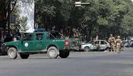Members of Afghan security forces inspect the site of a blast near Kabul University in Kabul, Afghan