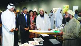 An Indian artist showing his work to Saif Saeed al-Dosari, P Kumaran and other dignitaries.